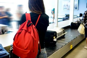 Girl with red backpack waits for her luggage at airport
