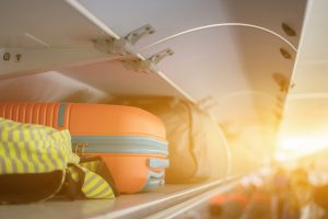 orange carry-on bag in overhead storage of plane