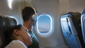 Couple on night flight looking out window
