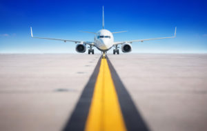 Airplane on runway with yellow stripe leading away from the camera
