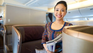 smiling flight attendant in business class on singapore airlines