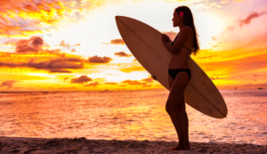 Surfer girl at sunset in hawaii