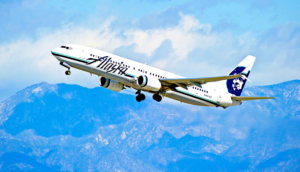 alaska airlines in flight with clouds in background