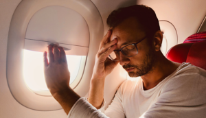Man trying to sleep on airplane with window open