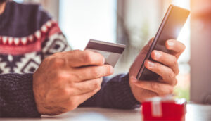 Man in festive holiday sweater holds credit card and iPhone