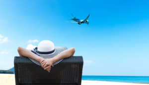 woman in beach chair in summer looking at airplane