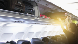 putting carry-on bag in overhead bin on airplane
