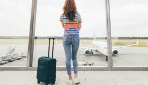 woman waiting for her flight with luggage