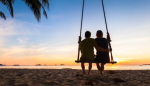 Couple on a swing watching the sunset at the beach