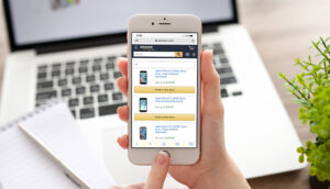 iphone screen with amazon trade in page up. hands touching home button