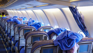 Cleaning staffs clean the airplane cabin including blankets, pillows and passenger seats.