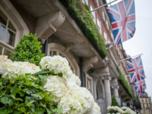 British-flags-flying-over-London-townhouse-with-flowers-blooming