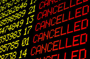 Arrivals and departures board at airport showing cancelled flights
