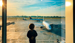 boy looking out window at airport at plane