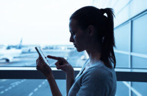 Woman in Airport Checks Smartphone