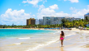 People on Isla Verde resort beach in Puerto Rico. Unrecognizable woman walking down the beach on summer holiday in bikini on famous Hispanic travel destination.