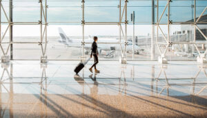 View on the aiport window with woman walking with suitcase at the departure hall of the airport.