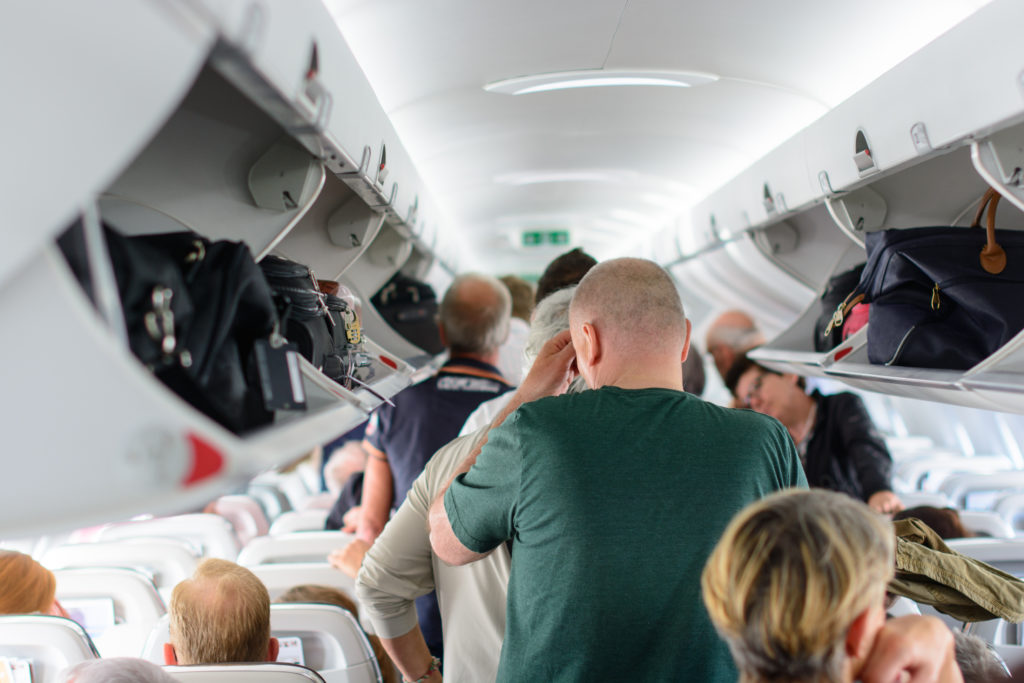 Airplane aisle crowded with passengers loading luggage into overhead bins