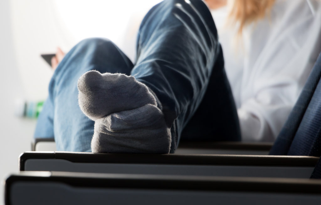 Woman with feet up on airplane seat