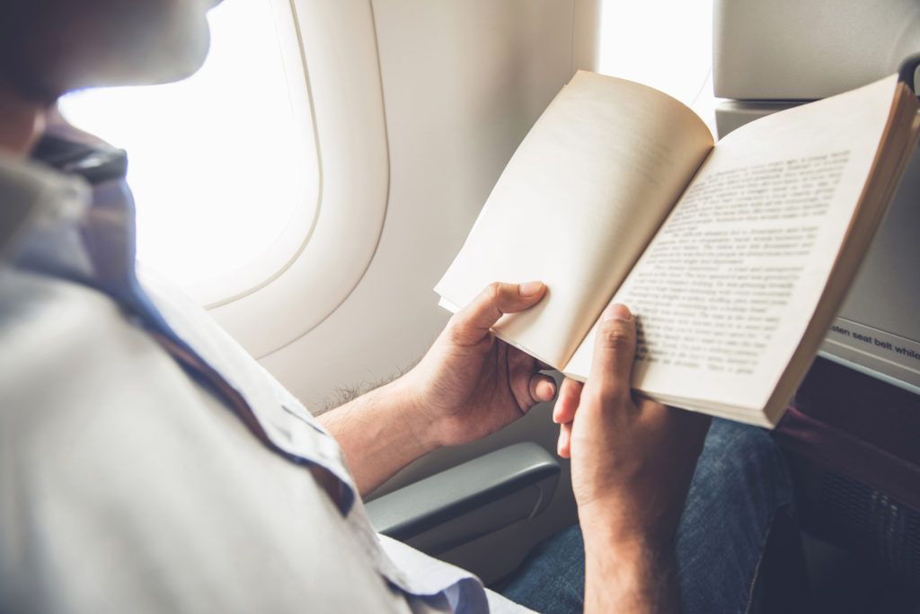 Man reading a book on a plane