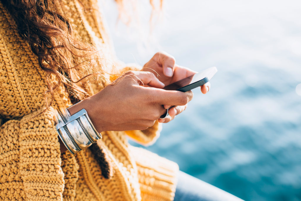 Woman in a yellow sweater texting