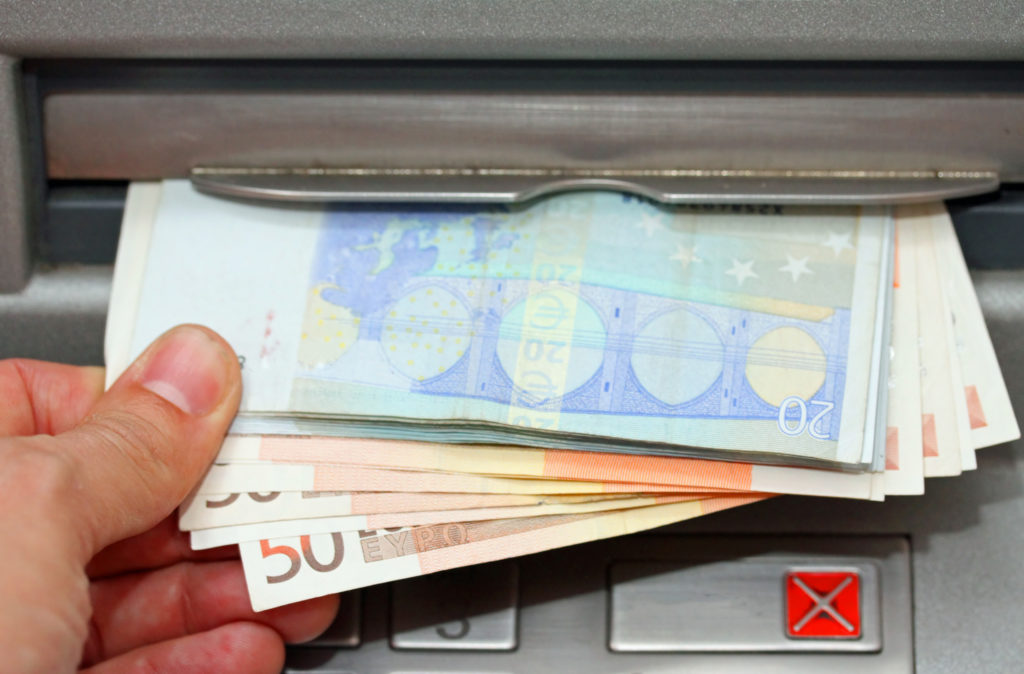 Hand withdrawing euros from an ATM