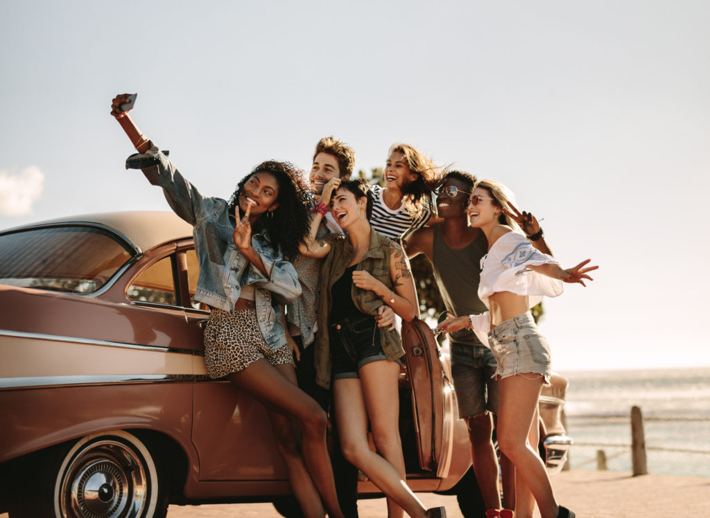 Group of friends taking a selfie by a car