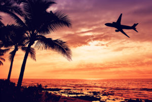 Airplane flying over a beach scene at sunset
