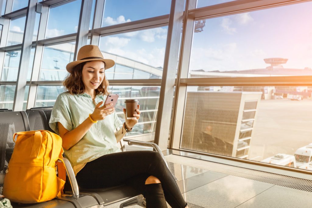 Woman using her phone, sitting in an airport terminal next to a yellow backpack