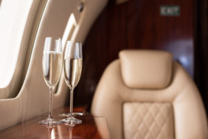 Two glasses of champagne on the side table of a first class airplane seat