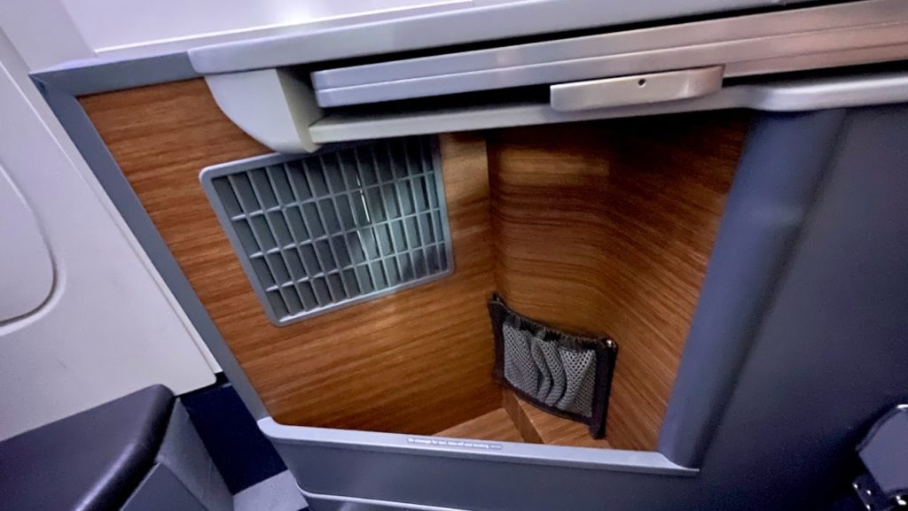 Storage center near plane seat in American Airlines business class cabin