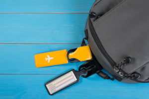Two luggage tags on a backpack on a blue background