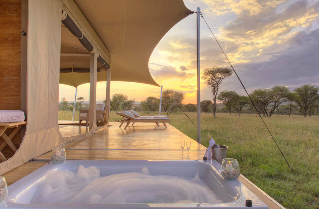 A bubble bath set into an outdoor patio attached to a large safari tent at sunset