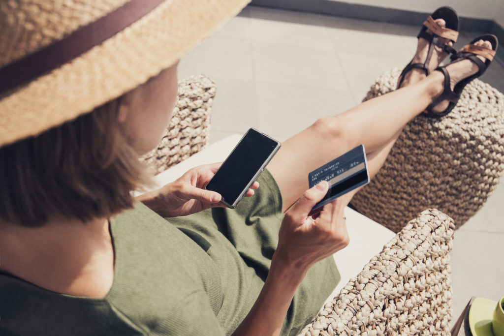 Woman making a purchase on her phone with her credit card