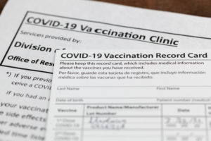 Close up image of COVID-19 vaccination record card and informational papers