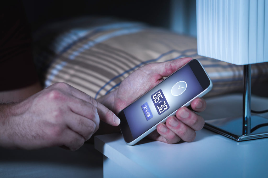 Person setting alarm on phone