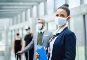 Masked flight attendant standing in airport