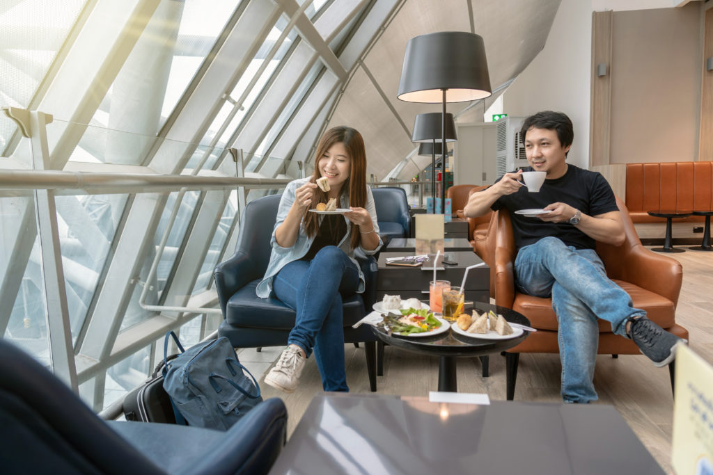 Couple sitting and eating in airport lounge