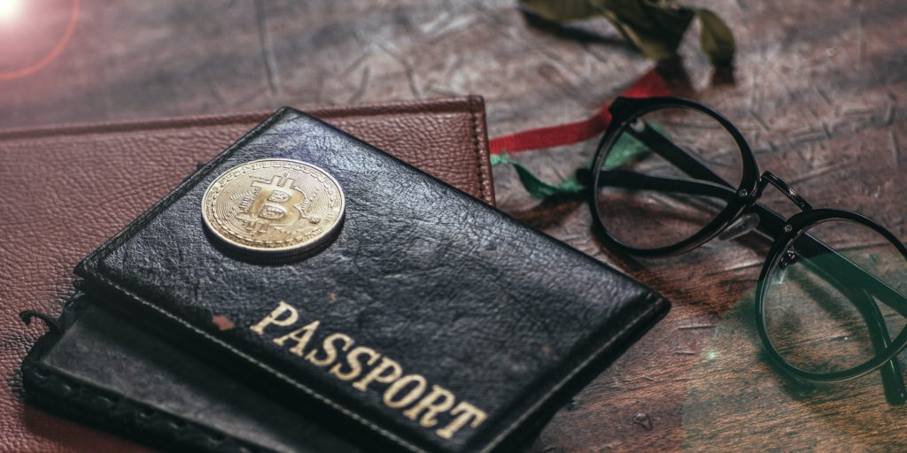 Physical representation of bitcoin on top of two passports, next to a pair of glasses, on a wooden table