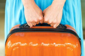 Woman in blue dress holding orange suitcase