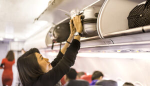 woman luggage carry-on overhead flight plane