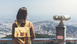 girl with backpack overlooking Barcelona, Spain from observation deck with tourist binoculars.