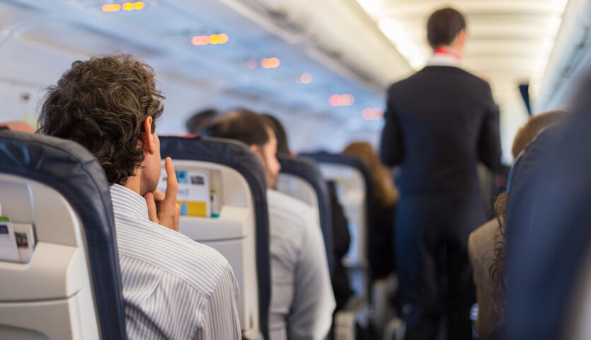 man thinking sitting in an aisle seat on an airplane