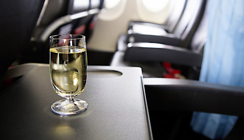 Wine on a tray table on an airplane