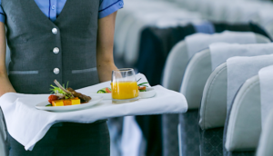 Flight attendant serving food onboard an airplane