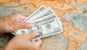 Hand with american money over a map