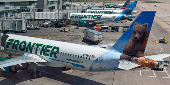 Frontier Airlines aircraft at Denver airport parked at gate with bear tail livery