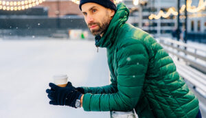 man wearing a puffy jacket and holding a coffee