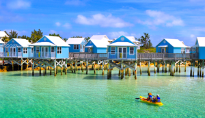 Alt tag not provided for image https://blog.airfarewatchdog.com/uploads/sites/26/2019/08/Hamilton-Bermuda-Kayak-Beach-StiltHouses-Atlantic-300x172.png