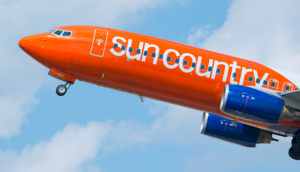 Sun country airplane taking off with logo on side of plane